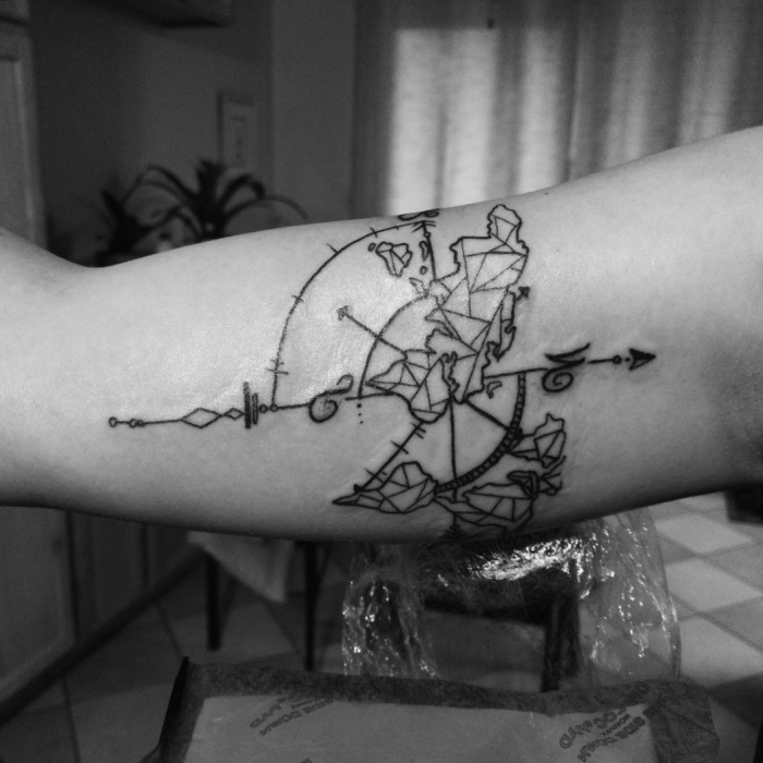weltkarte tattoo am oberarm, geometrische motive, die erdtieile, dünner pfeil