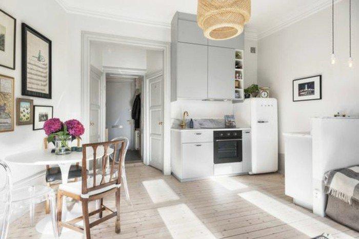 einzimmerwohnung einrichten ideen, weiße wohnung gestalten, runder kleiner esstisch mit holzstühle und küchenzeile, sofa rechts