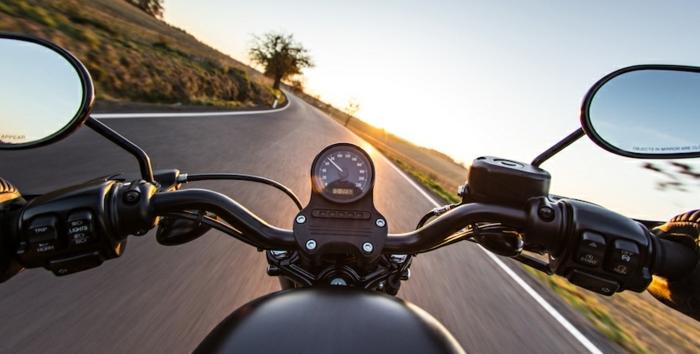 ein Motorrad auf der Landstraße fotografiert beim Sonnenaufgang, zwei Spiegel, 5G Netzwerk