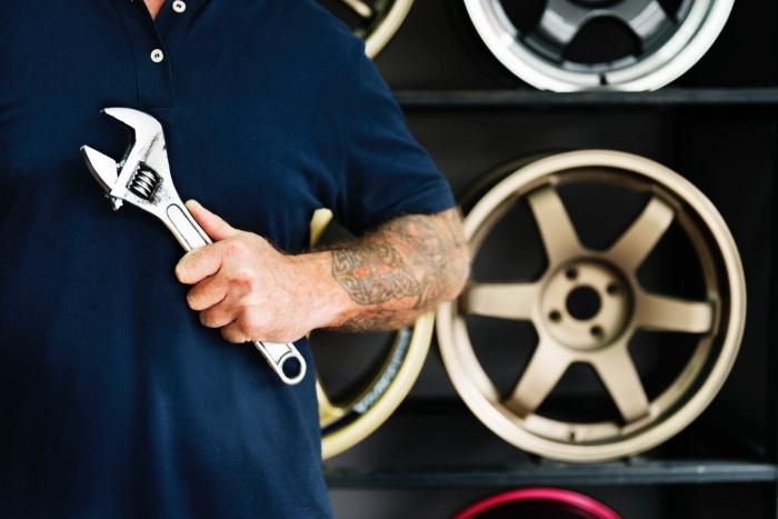 auto garage einrichten, hilfreiche tipps, großer schraubenschlüssel, tattoo am unterarm, auto reparieren