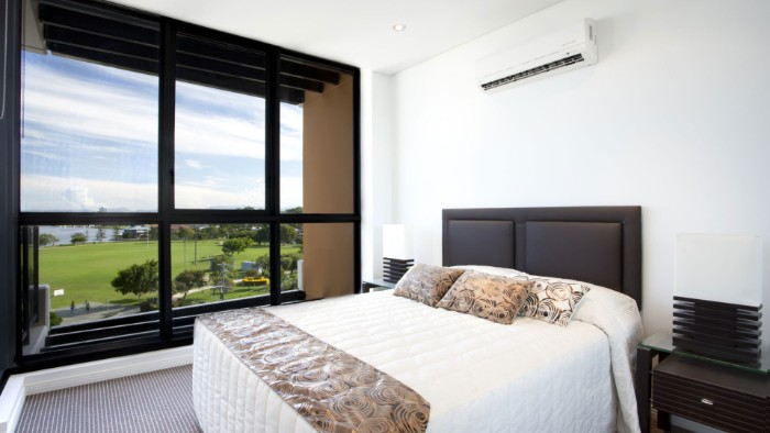wohnzimmer mit einer weißen wand mit weißer klimaanlage, weißes bett und ein fenster, wohnzimmer einrichtung