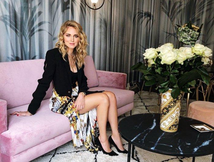 Chiara Ferragni auf einem pinken Sofa, schwarze Schuhe, die aus Ihrer Kollektion stammen