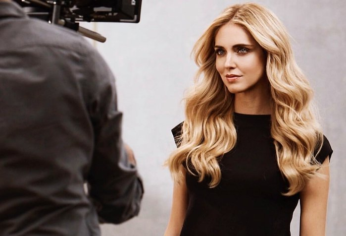 ein Mensch mit Kamera filmt Chiarra Ferragni, die schön frisiert ist und leicht lächelt, sie trägt schwarzes Kleid