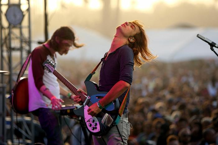 Tame Impala sing für Coachella, der Sänger spielt Gitarre vor einer großen Menge wie auf dem Festival