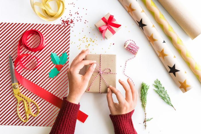 diy geschenke selber machen, braune verpackungspapier, rote schleife, große schere, weihanchtsgeschenk