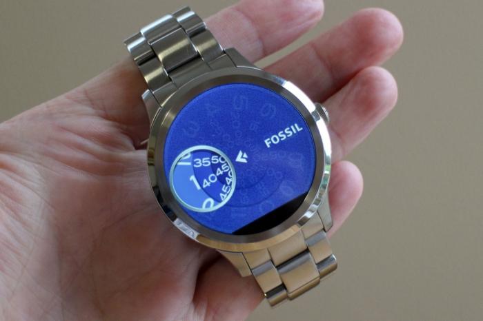 eine Smartwatch von Fossil mit einem blauen Display in einem Hand