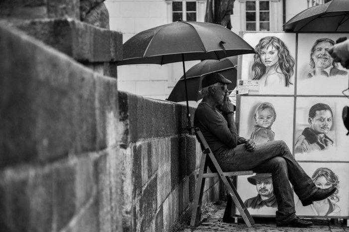 Mädchen zeichnen, eine Menge Zeichnungen, ein Maler, die Porträt verkauft sitzt vor den Werken