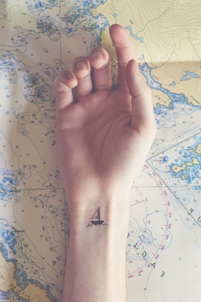 mini tattoos ideen, ein kleines schiff auf der hand, handgelenl , eine hand liegt auf weltkarte