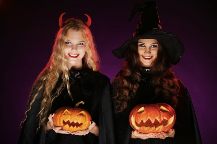 halloween kostüme und ideen, zwei frauen wie hexen verkleidet, schwarze mäntel, kürbis leuchten,, dunkellila hintergrund