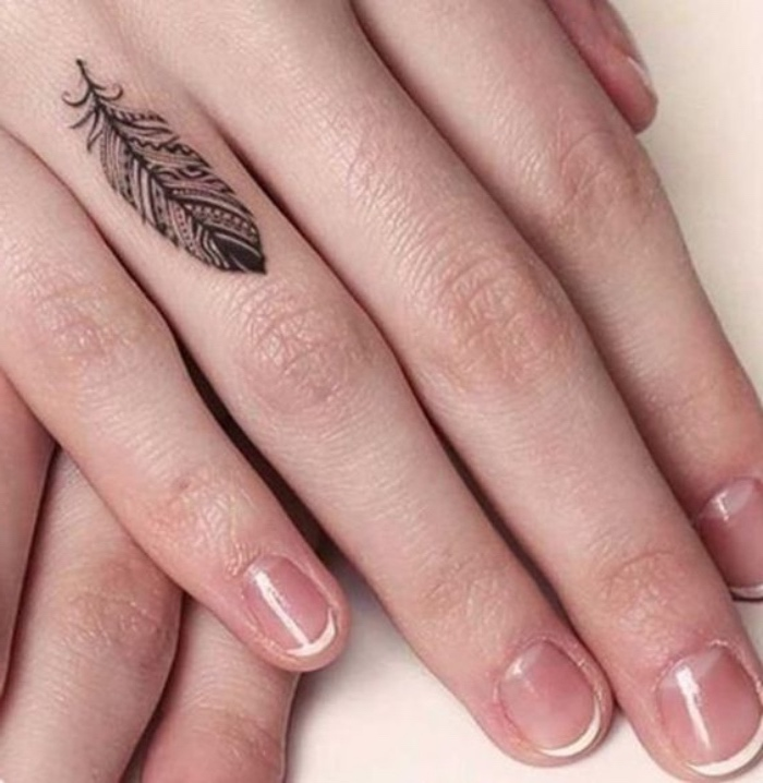 tattoo ideen auf dem finger, ringfinger, eine feine hand von einer frau, french nägel, federtattoo