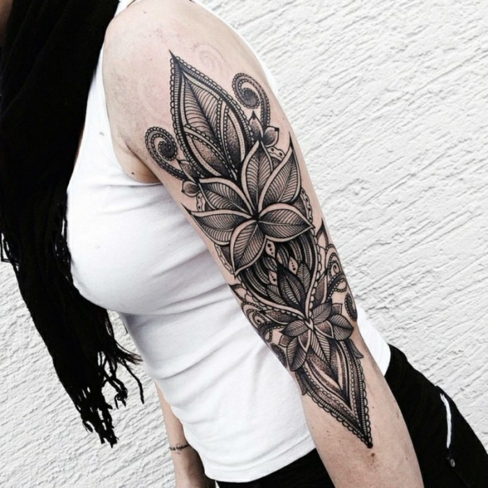 frau mit schwarz graues oberarm tattoo, florale und geometrische motive, arm tätowieren