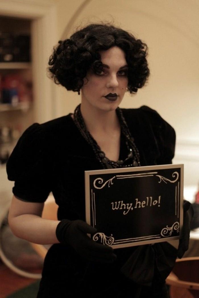 gruselige kostüme, eine theater schauspielerin in schwarzer verkleidung, kurze haare, kleid mit decollete und schwarze perlen