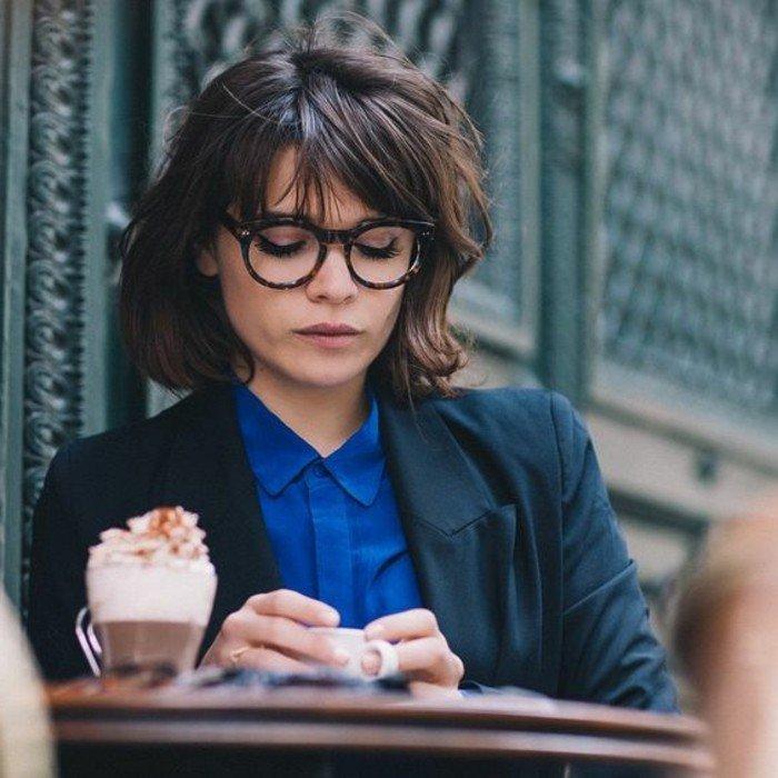haarfarbe ändern ideen für braune nuancen und frisuren, kurze haare, nicht gestylt, eine frau mit lesebrille steht am morgen im cafe