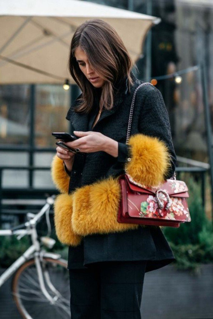 schöne haarfarben, haare schneiden und färben in braun, elegante moderne frau mit schwarzem mantel und gelbe flauschige accessoires dazu