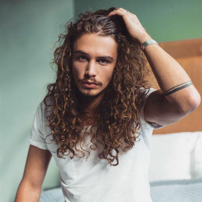 naturlocken frisuren für lange männerhaare, braunes haar mit kleinen locken, mann mit tattoo am arm