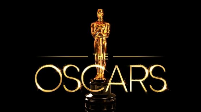 eine Skulptur von Oscars, auf einem schwarzem Hintergrund, goldene Skulptur und goldene Aufschrift