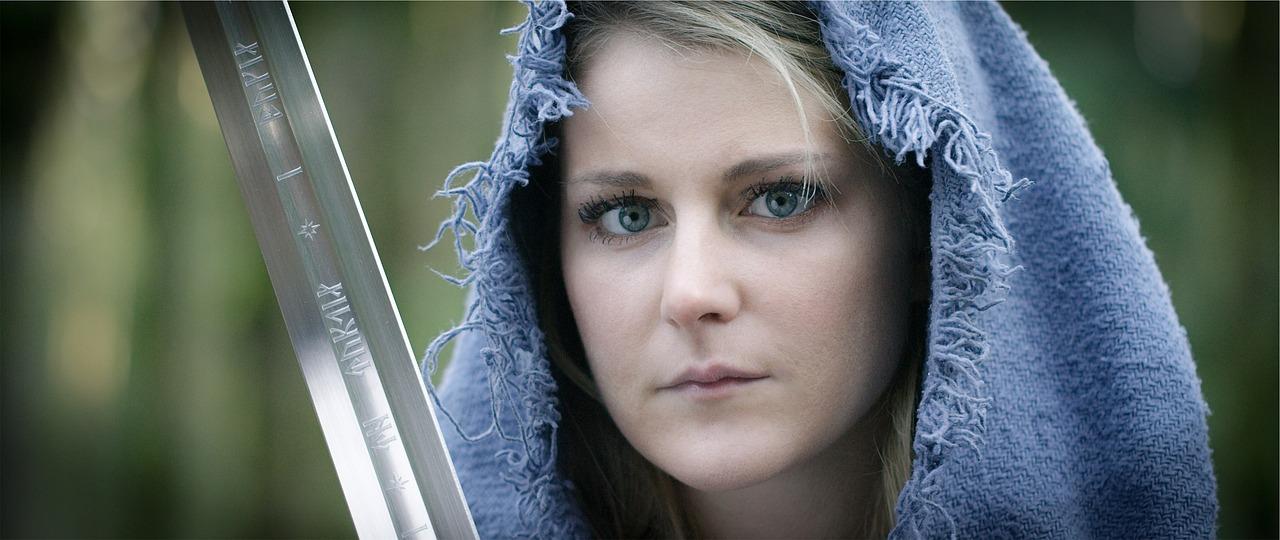 ein blondes Mädchen, das LARP mitspielt, ein Schwert mit Schrift, eine blaue Kapuzel,