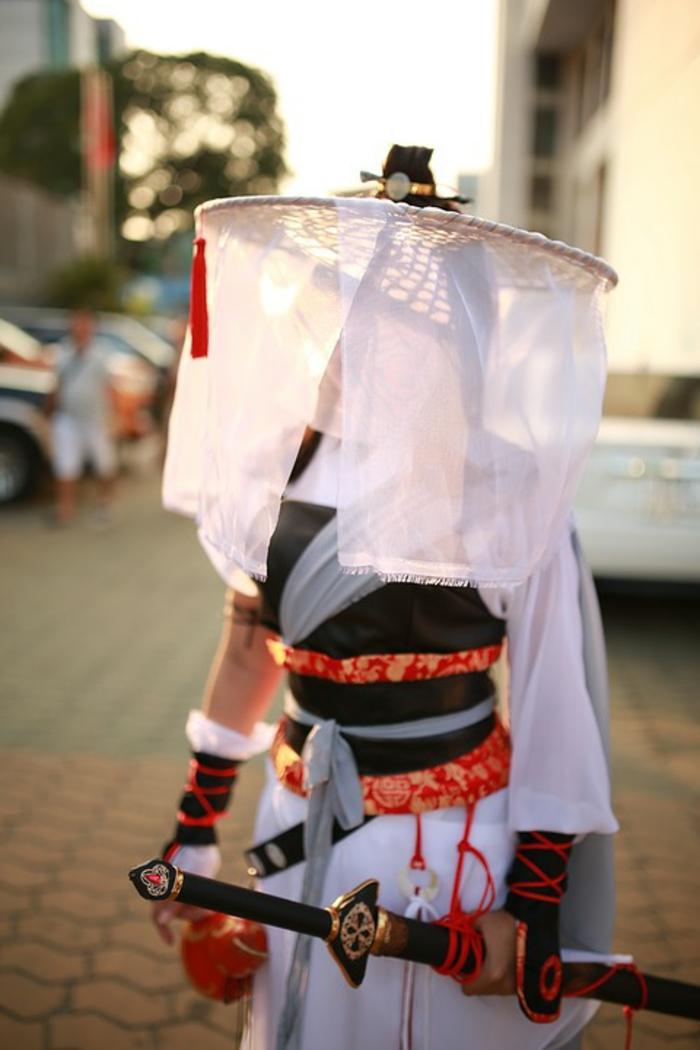 Ein Mädchen mit Kostüm und Katana Schwert, ein Samurai Ninja Kostüm in weißer Farbe