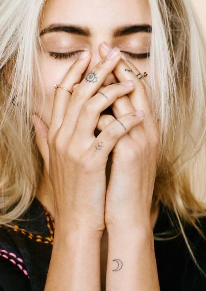 mini tattoos, ideen für körperverzierung für frauen, kleine deko zeichnungen auf den fingern einer blonden frau