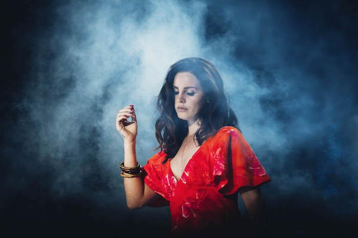 Lana Del Rey in rotem Kleid mit weiten Ärmeln, schwarze wellige Haare, matter Lippenstift und schwarzer Eyeliner