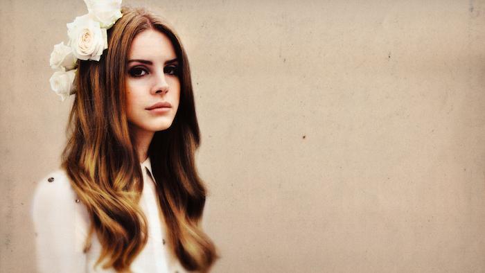 Lana Del Rey mit weißen Rosen im Haar, hellbraune wellige Haare mit Mittelscheitel, Smokey Eyes und matter Lippenstift