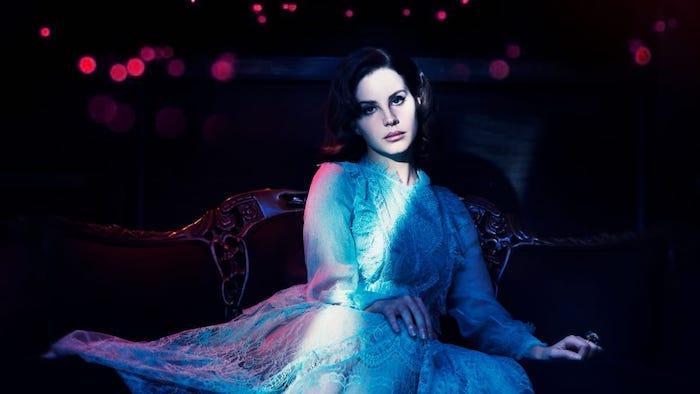 Lana Del Rey in weißem Spitzenkleid mit langen Ärmeln, schwarze Haare und Porzellanteint