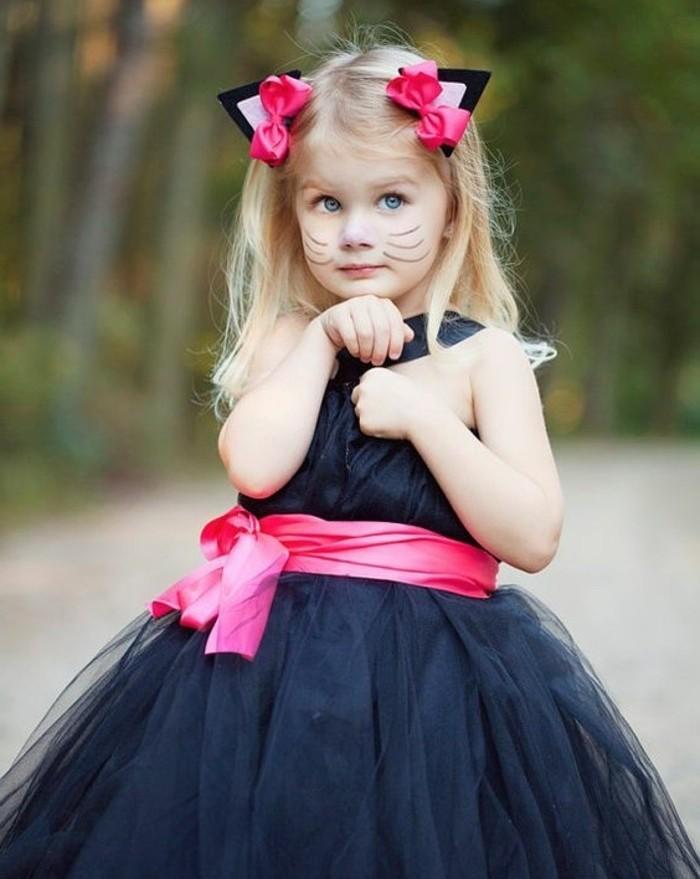 halloween kostüm ideen zum nachmachen, ein kleines mädchen mit blonden haaren und diadem mit katzenohren, gesicht schminke als katze für kinder, elegantes kleid mit rosaroter schleife