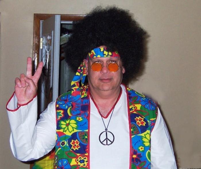 halloween kostüm ideen, hippie style mann, weißes hemd, buntes oberteil, große haare, kleine runde sonnenbrille in oranger farbe