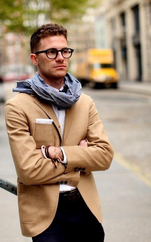 kurze haare locken, ein sportlich eleganter mann mit beigem blazer, schwarze hose, weißes hemd, schal und brille, kurze frisur