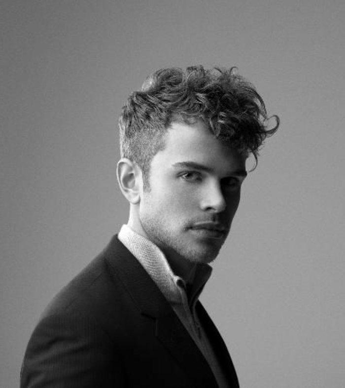 schwarz weißes foto von einem model mann, frisuren halblang gestuft locken, natürliche haare