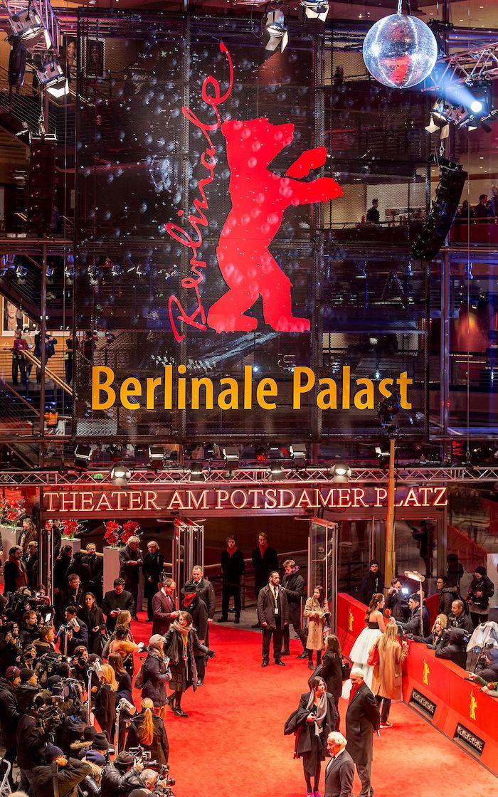 theater am potsdamer palast und viele menschen und rotter teppich, logo bon berlinale mit einem roten großen bär