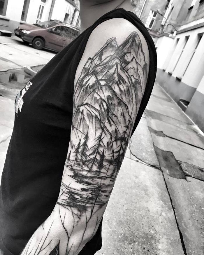 frau mit oberarm tattoo, gebirge und see, tätowierung in schwarz und grau, blackwork