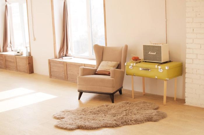 beige ohrensessel, sessel mit dekokissen, tisch aus rotro koffer, flauschiger teppich