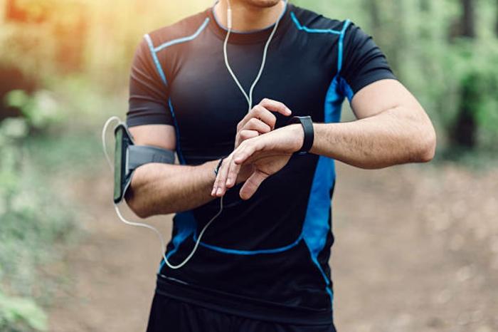 ein Renner mit Smartwatch, Trainingsanzug in schwarzer und blauer Farbe, Handy und Smartwatch an dem Hand