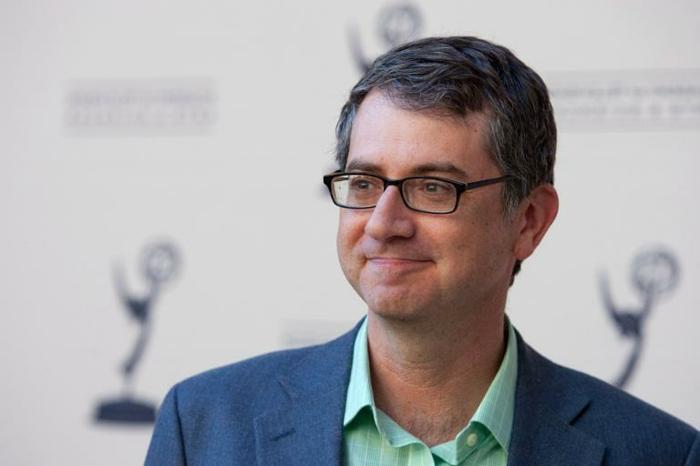 Greg Daniels bekommt Emmi Preis, blaue Jacke ein grünes Hemd auf weißem Hintergrund