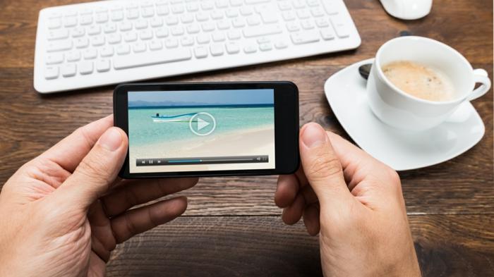 ein Bild vom Meer und ein Boot, ein Foto vom Handy, eine Tastatur, eine Kaffeetasse, Swipe-Navigation