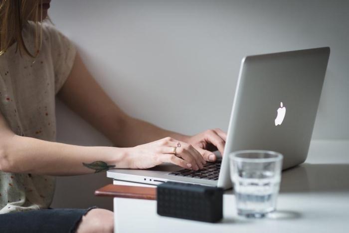 frauen tattoo, eine frau arbeitet am computer am abend, hönde am schreibtisch und ein federtattoo