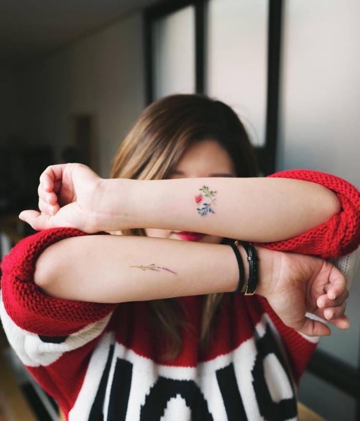 tattoo ideen für frauen, die zwei hände von einer frau werden tätowiert, roter pulli, man sieht das gesicht von der frau nicht