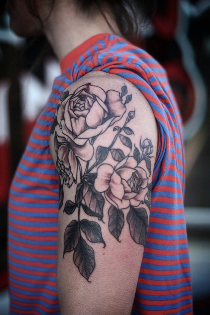 tattoo oberarm frau, tätowierung mit rosen als motiv, gestreifte bluse in rot und blau