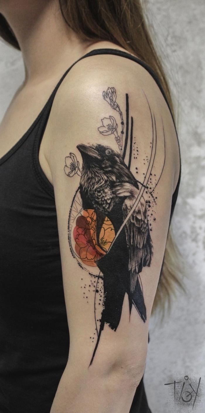 tattoo oberarm frau, vogel als motiv, schwarzer rabe, kleine blüten
