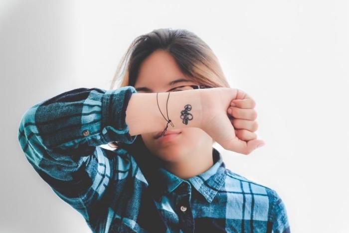 tattoo klein neben den armbändern, blau, schwarzes hemd, mädchen tattoos
