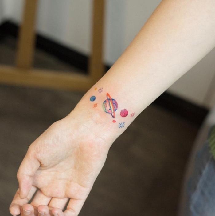 tattoo klein mit vielen planeten das sonnensystem am handgelenk, arm foto