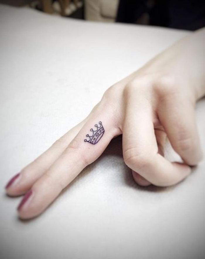 tattoo motive, eine kleine krone am inneren vom finger, mittelfinger tattoo, königliches element