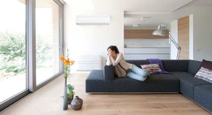 wohnzimer einrichtung, vase mit orangen blumen, eine lampe und eine weiße klimaanlage im wohnzimmer