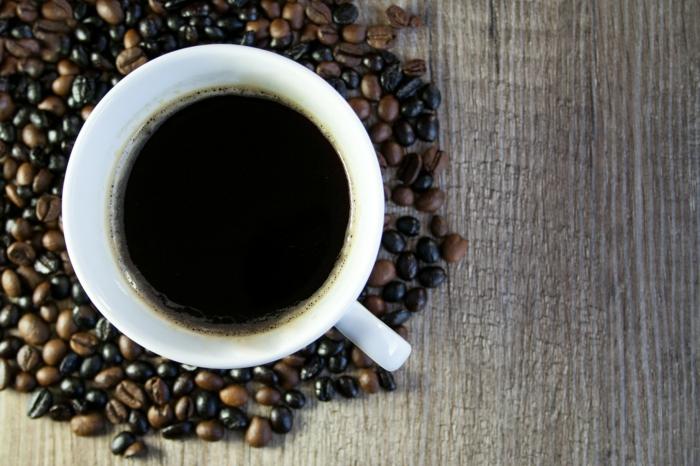 eine Tassee Kaffee, Kaffeebohnen, ein Tisch aus Holz, weiße Tasse, Tassen als Werbegeschenk