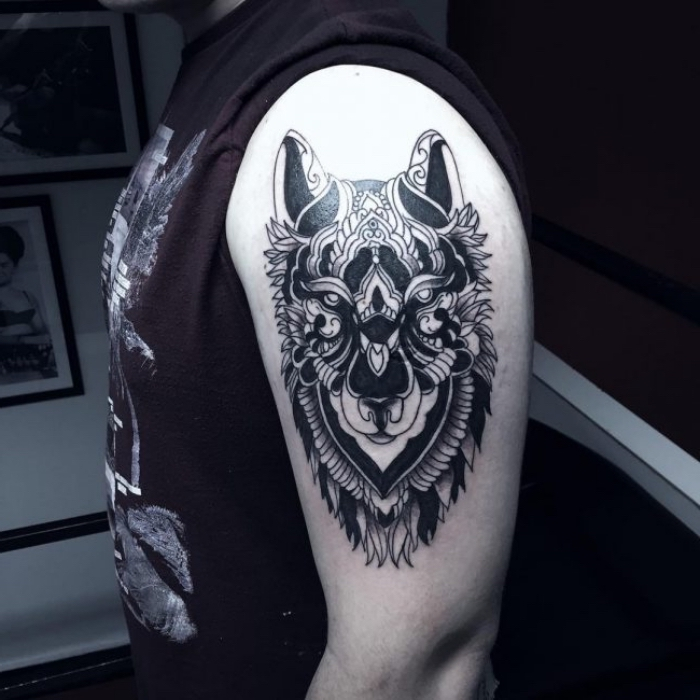mann mit wolf tattoo am arm, blackwork tribal tätowierung, wolfkopf