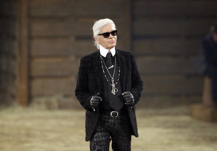 der designer karl lagerfeld mit einem schwarzen anzug und mit schwarzen sonnenbrille und langen halsketten und schwarzer sonnenbrille