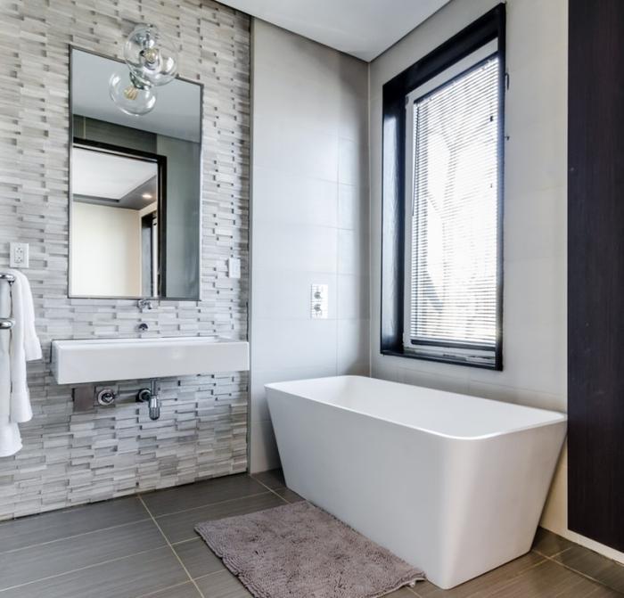 badspiegel auswählen, badezimmereirncihtung in weiß und grau, graue bodenfliesen, ziegelwand
