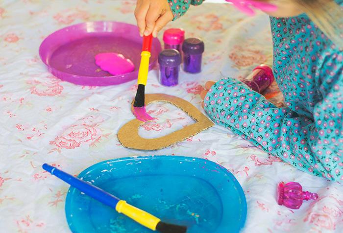 Bastelideen für Kinder, ein kleines Mädchen malt in rosarot ein ausgeschnittenes Herz aus Karton, Lila Teller, Blauer Teller