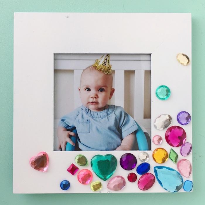 Weißer Bilderrahmen aus Holz, dekoriert mit bunten Steinen, süßes Baby mit Partyhütchen auf dem Bild